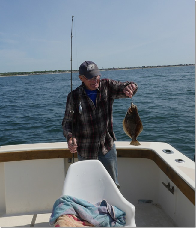 Captain Earl catches the first flounder on our ri flounder fishing trip